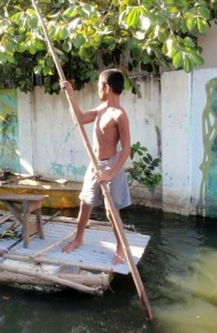 A boy rows a skiff down a flooded street in Rizal Province, Philippines